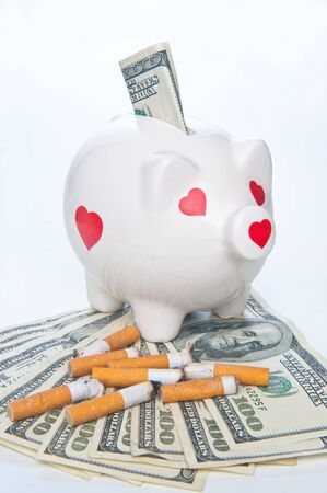 piggybank and cigarette butts standing on money photo