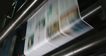Print plant factory. Newspaper printing at a plant. Newspaper printed on a printing house machine. Close up