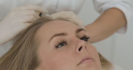 Young attractive woman receives mesotherapy for hair. Girl receives an injection in the head. Close up.