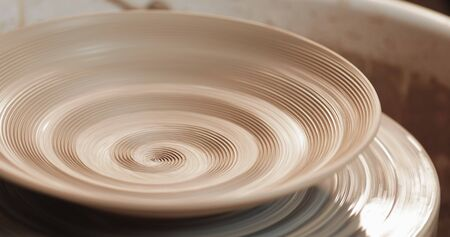 An empty plate with relief rotates on the pottery wheel, close up. Winding clay structure. Handmade, craft. White clay.