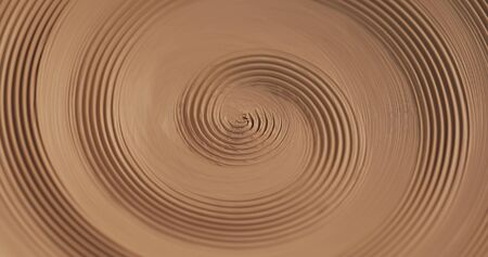 An empty plate with relief rotates on the pottery wheel, close up. Winding clay structure. Handmade, craft. White clay. Top view.