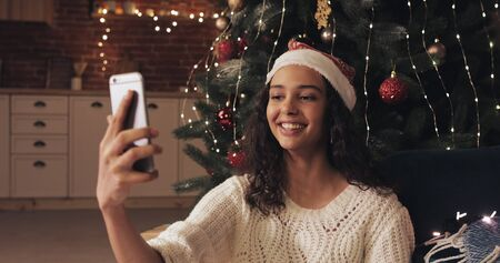 Young Attractive Woman Wearing Christamas Hat Sitting near Decorated Christmas Tree. Woman Making Selfie on her Samrtphone and Sending it. Concept of Holidays and New Year.