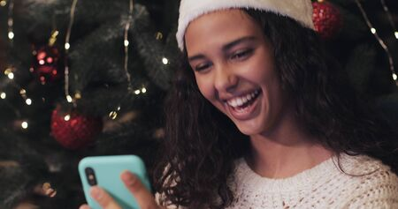 Close Up of Happy Smiling Pretty Girl in Santas Hat Using her Smartphone and Laughing while Sitting at Christmas Tree at the Background. Holiday Concept.