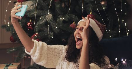 Young Attractive Girl Wearing Christamas Hat Sitting near Decorated Christmas Tree, Making Selfie, Posing, Showing Tongue, Smiling. Concept of Holidays and New Year.