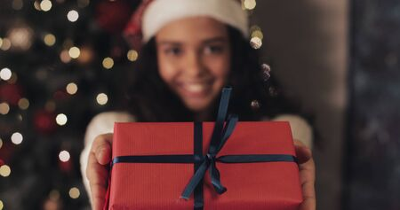 Young Smiling Girl in Santas Hat Gives the Red Present Box with Blue Ribbon to Camera, Standing at Christmas Tree Lighting at the Background. Happy Holiday Concept. Close Up.
