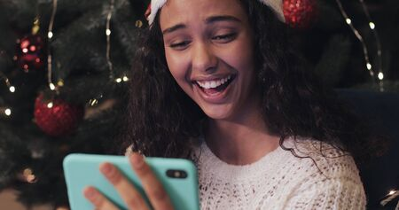 Happy Beautiful Mulatto Girl in Santas Hat Sitting at Christmas Tree at the Background, Using her Smartphone, Looking at the Screen and Laughing. Holiday Concept. Close Up