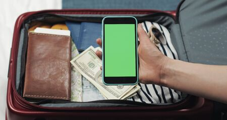 Young woman getting ready for a trip. She holding smartphone with green screen on the suitcase background. Chroma key. Фото со стока