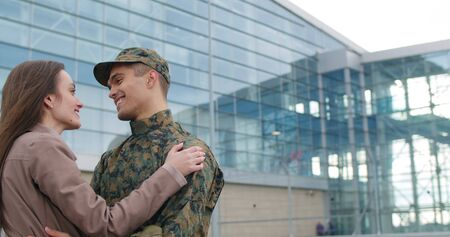 Happy man in camuflage returning from army and welcomed by his wife. Smiling soldier and his girlfriend talking and standing at airport. Concept of happy reunion. Close up