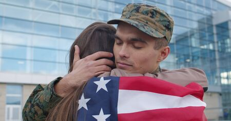 Close up of happy soldier embracing his wife covered into american flag. Happy family meeting of military man. Young man retired from army and meeting his girlfriend. Long awaited meeting