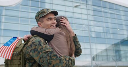 Soldier man in camouflage uniform standing and embracing his loved one. Portrait of happy couple with romantic reunion. Soldier hugging wife with american flag in her hand. Crop view