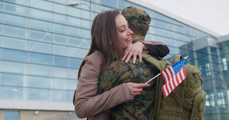 Happy wife meeting his military husband after returning from military service. Young patriotic girl running and cuddling to his boyfriend in military uniform.Concept of military service Фото со стока
