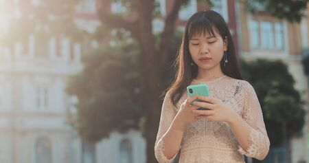 Attractive asian girl standing with smartphone and waiting friend at city street. Young woman in stylish dress standing outdoors and using mobilephone. Concept of communication and people Фото со стока