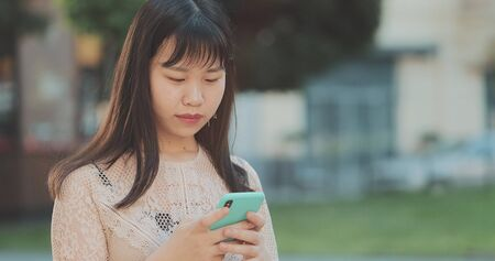 Close up of businesswoman in casual clothes standing at street and checking news at smartphone. Woman using phone for chatting and texting sms outdoors. Concept of business and communication