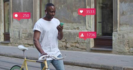 Young African American man using smartphone walking with stylish modern bike at old town. Animation with user interface with follower, comments, likes counting bubble from smartphone. Social media concept