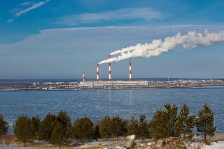 Industrial landscape with the steam from the pipes thermoelectric power station on a background of blue sky and the river in winter Stock Photo