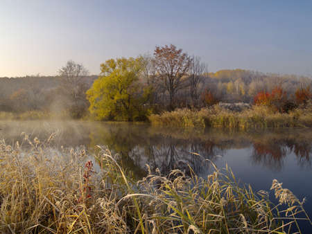 A landscape with an autumn wood lake and the first morning hoarfrost