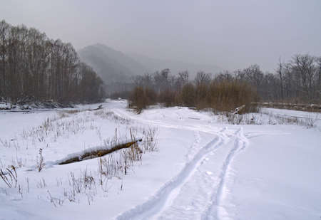 Landscape with the frozen river and mountains in a fog