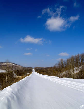 Winter landscape with road and wood photo