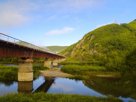 Morning landscape with the railway bridge at a mountain slope photo