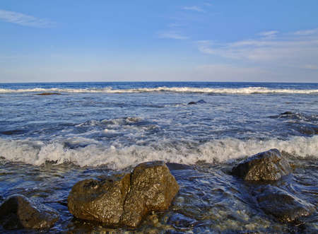 Sea surf and boulders in the foreground
