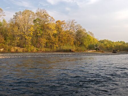 Autumn in the evening on bank of small river