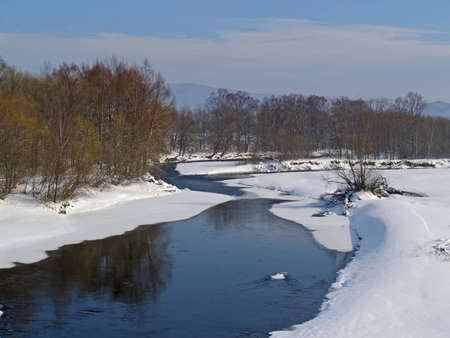 Winter landscape with the river and snow-covered coast