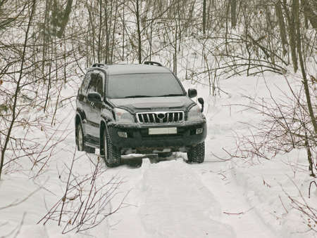 The off-road car covered with snow in winter wood Stock Photo