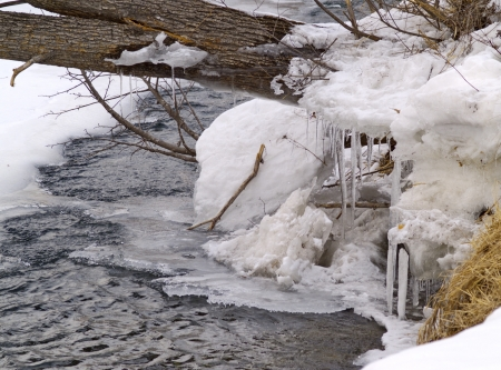 At snow-covered coast of the spring river Stock Photo
