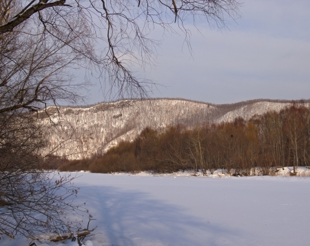 Winter landscape with the frozen river at a mountain slope