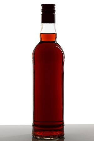 botella de whisky: Una botella de coñac sobre un fondo claro