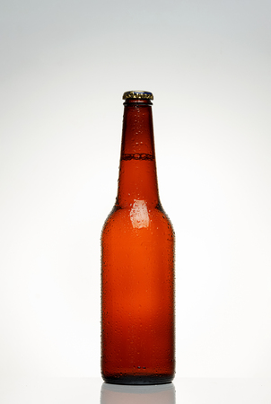 chilled bottle of beer on the gradient background water drops