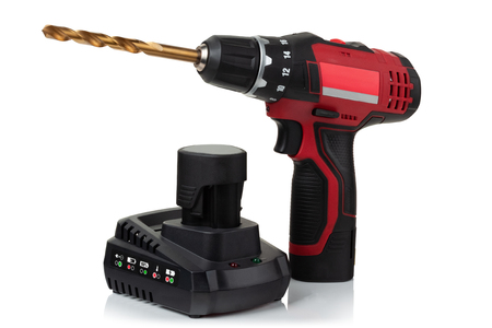 modern compact cordless screwdriver, drill with drill and charger with battery on white background