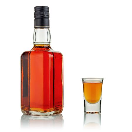 A bottle and a glass of alcohol on a white background.