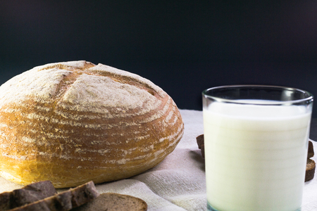Background food ingredients on the tablecloth. Homemade bread and milk.