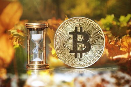 The physical bitcoin and hourglass show the time is coming and autumn is came