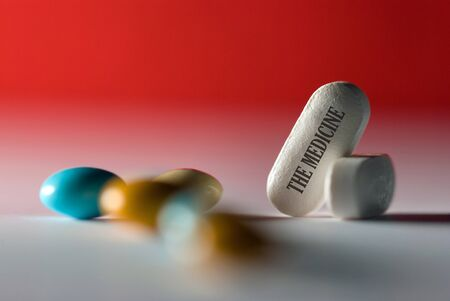 The medicine,  inscription on pill, scattered tablets on red background, concept Stock Photo