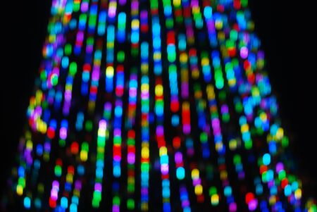 Defocused Glare from the background of the Christmas tree, against the night sky, a festive background.