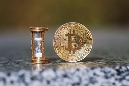 Physical bitcoin and hourglass showing that time goes by