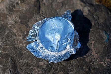 inflation, a wrapper made of foil in the form of bitcoin lies on the snow Stock Photo