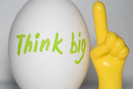 Think big -  the inscription on a white chicken egg, in bright letters in green and a yellow plastic hand with the index finger pointing upwards on a white background. Thinking concept