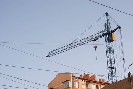 Construction crane on a background of blue sky