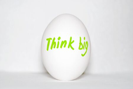 Think big -  the inscription on a white chicken egg, in bright letters in green on a white background. Thinking concept