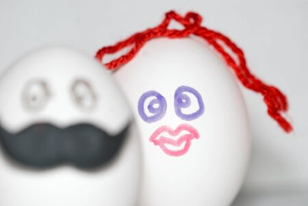 Two eggs decorated under a man in the foreground, with a large mustache and a woman on the background, with red hair, as bride and groom, a couple concept