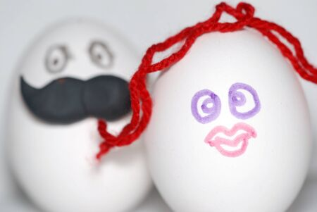 Two eggs decorated under a man on the background , with a large mustache and a woman in the foreground, with red hair, as bride and groom, a couple concept Stock Photo
