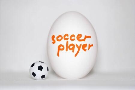 Jugador de fútbol: una inscripción en un huevo de gallina blanco en letras de color naranja brillante y un balón de fútbol sobre un fondo blanco. Juego para principiantes, concepto Foto de archivo