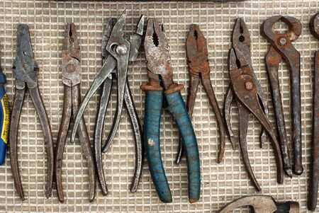 a set of old rusty pliers for work laid out on the floor