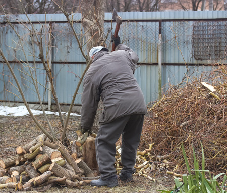 photo image of man who chopping woods in the spring garden in the day