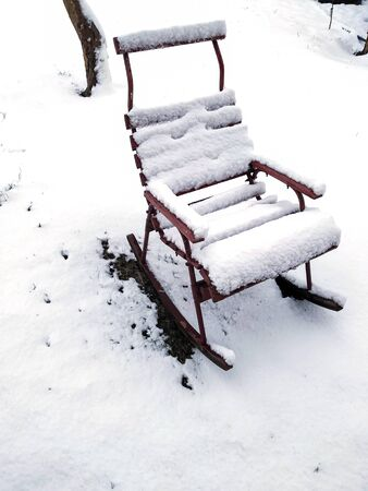 photo image of the lounge chair covered by the snow in the winter garden Standard-Bild