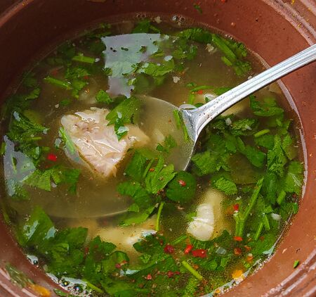 photo image of the soup with meat, parsley, potato in the brown plate on the table Standard-Bild