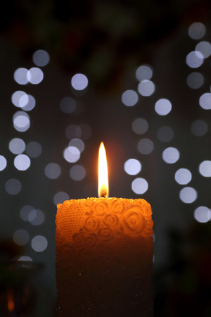 christmas church: burning candle on blurred background